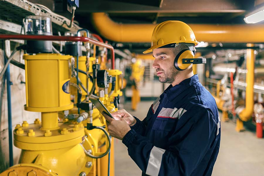 Technician in protective gear checks industrial pumps and other machinery